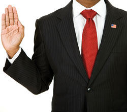 Photograph of a man taking an oath with right hand raised